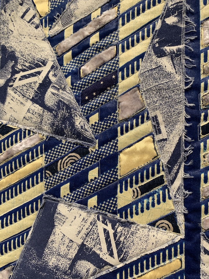 vertical section of navy blue, gray, and yellow quilt art, stitching on strong varied diagonal lines